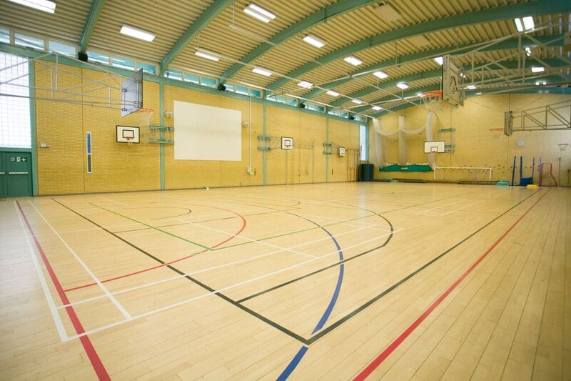 Large student sports hall with basketball hoops and other sports equipment at Sir William residential summer camp