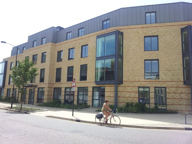 Student bikes to their English lessons past Bragg House residential accommodation at Sir Michael summer camp in Cambridge