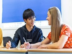 An image of a student smiling in English language lessons at Studio Cambridge, linking to a page on General & Intensive English Courses where you can find out more about learning English in Cambridge