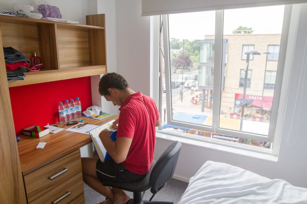 A student in his room at Bragg House accommodation. Rooms are single en-suite with a desk.