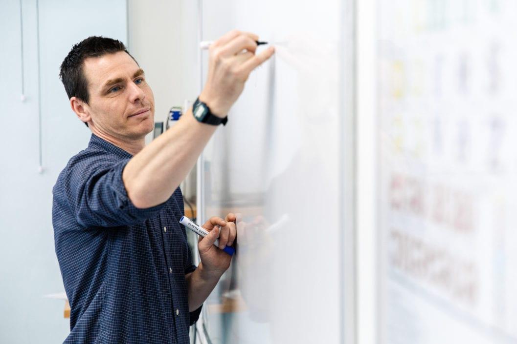 Teacher writes on a board in class at Studio Cambridge