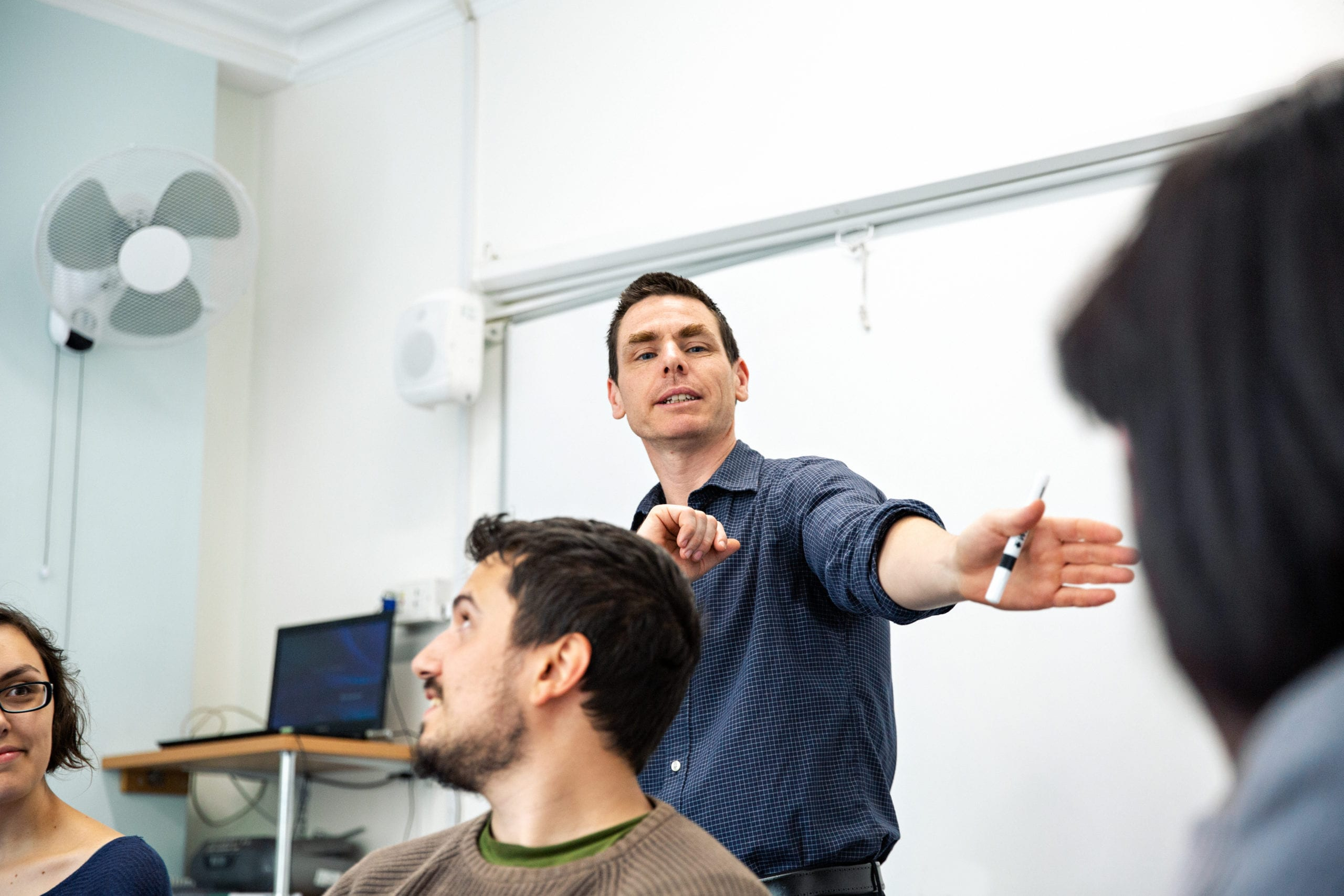 A teacher teaches to adult students in a class at Studio Cambridge