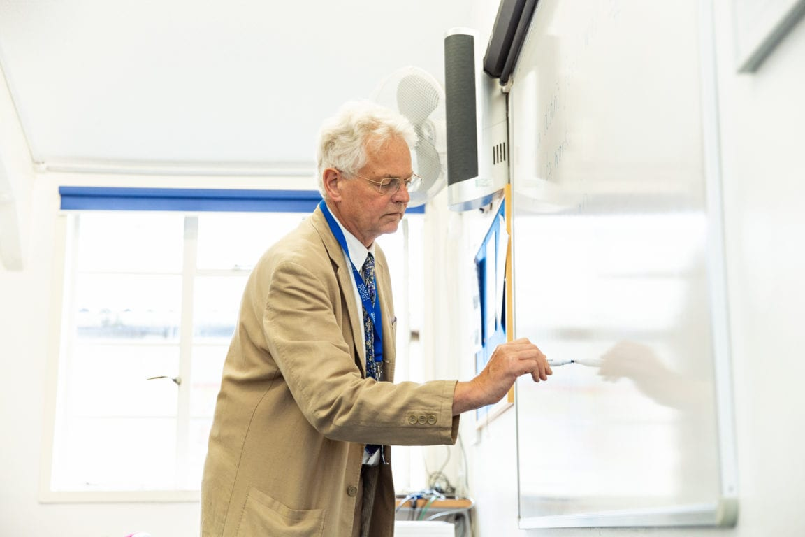 A teacher writes on the board in a lesson at Studio Cambridge