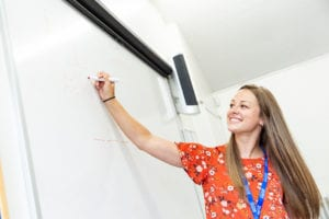 Studio Cambridge teacher smiles as she writes on a white board in a lesson.