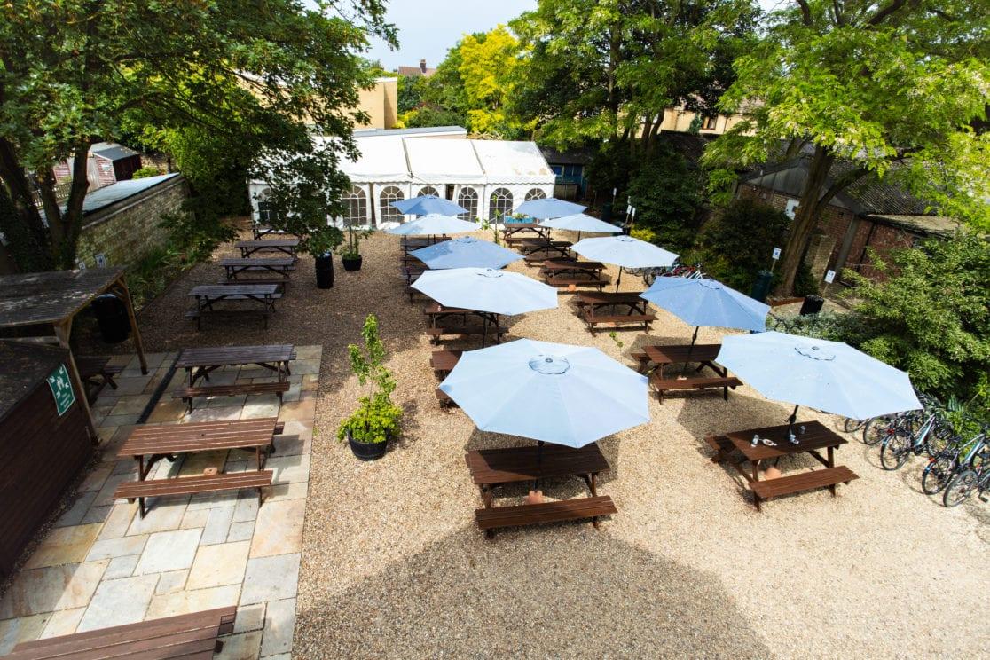 Tables and umbrellas on a sunny day in the Studio Cambridge garden.