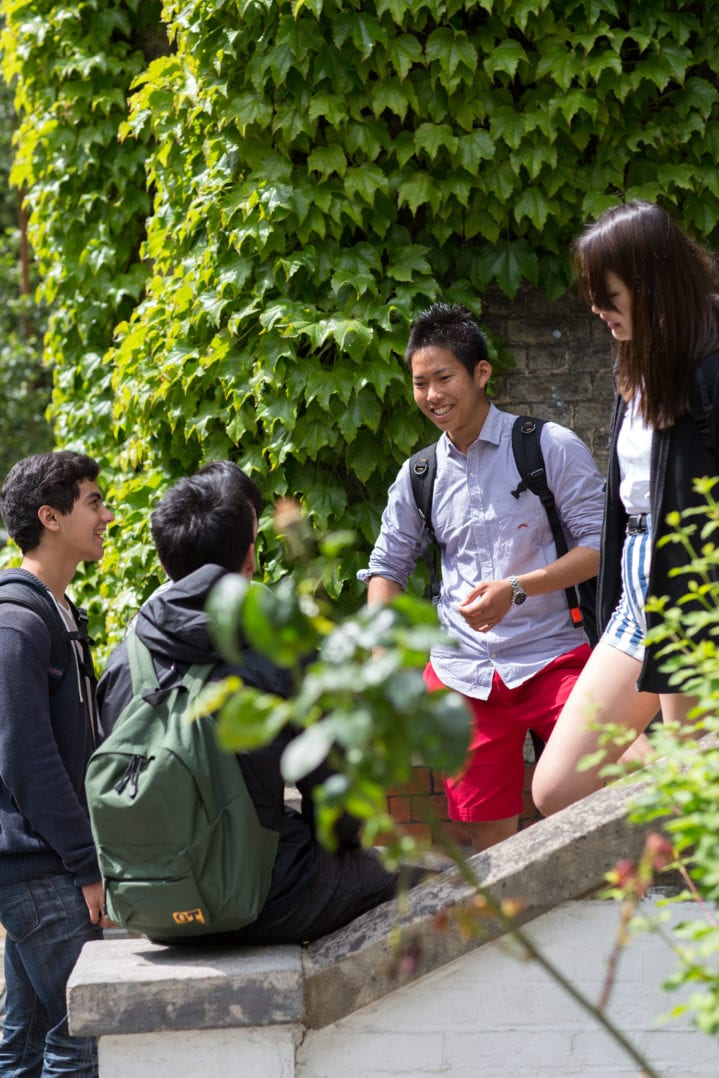 A group of new friends laugh on the steps outside the main school at Studio Cambride