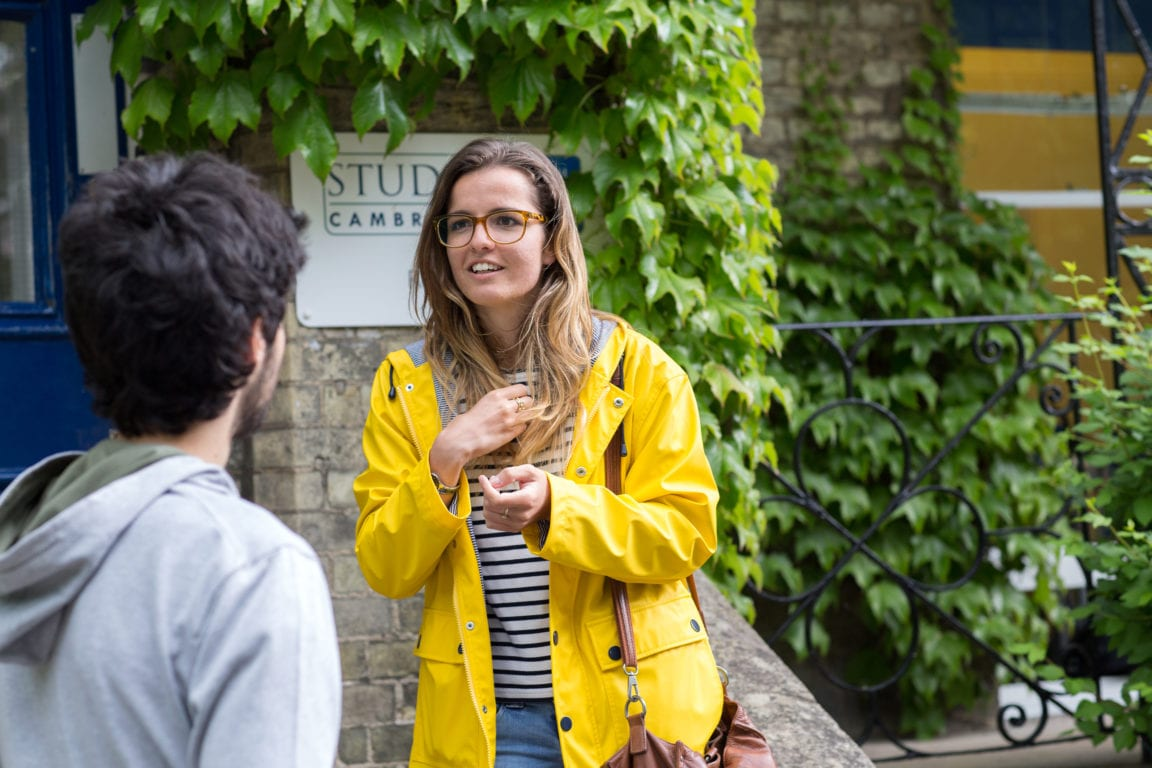 Female student wearing a yellow coat stands outside of the main school at Studio Cambridge