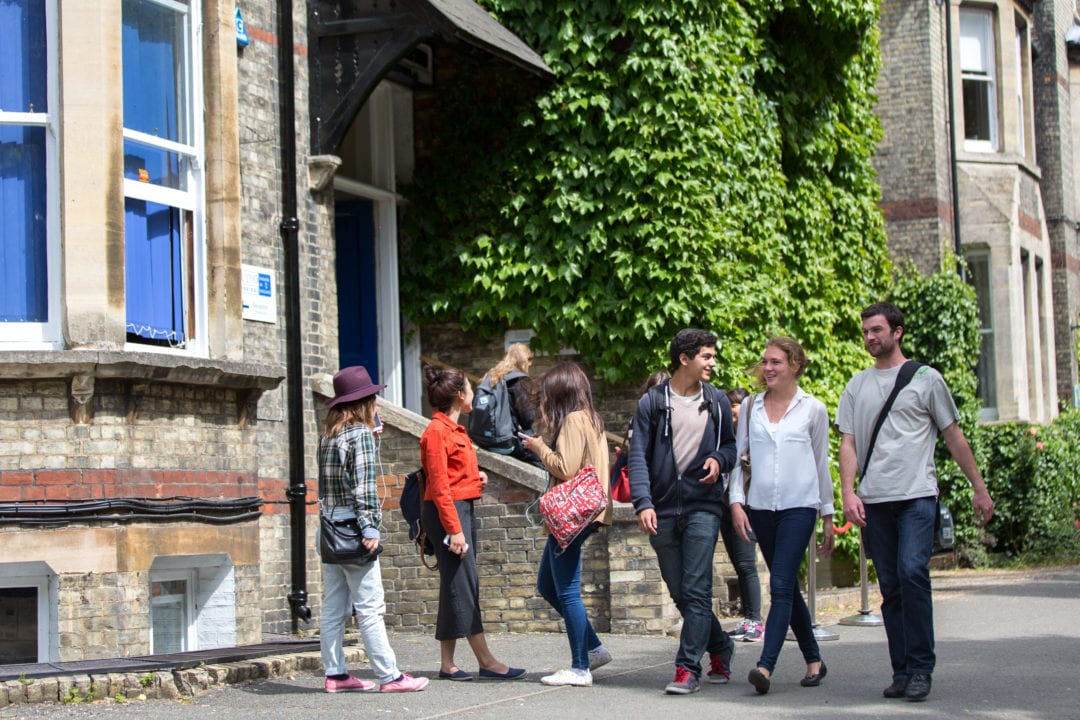 Students talk and smile as they walk in front of the main school at Studio Cambridge