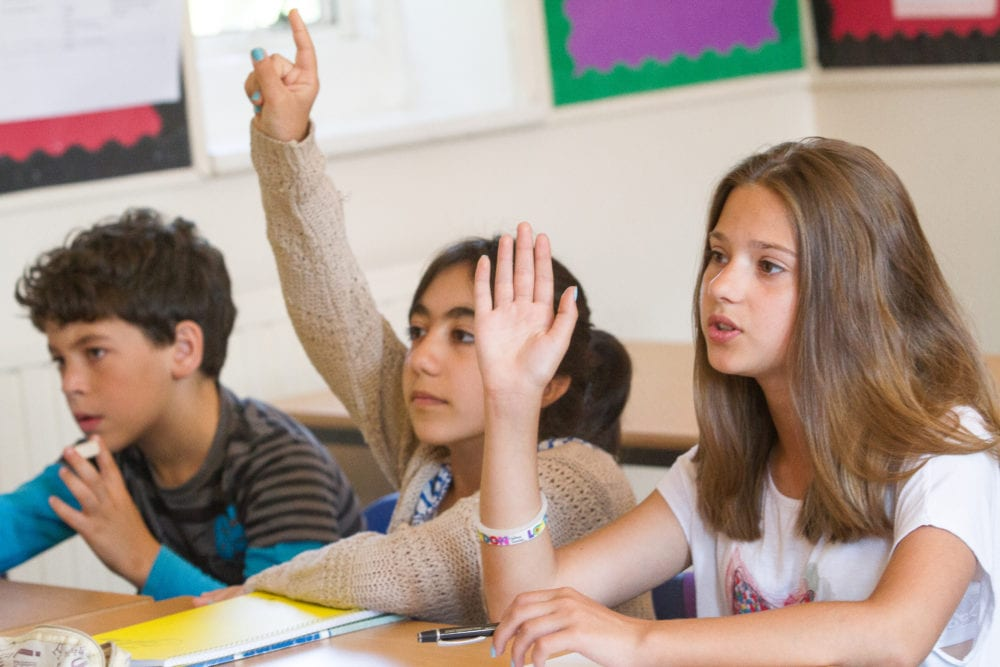 Two students raise hands to answer English teacher's question at Sir Henry residential English summer camp