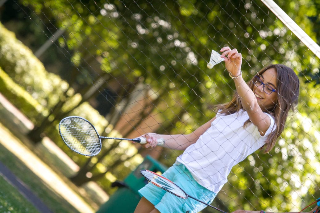 Student prepares to serve shuttlecock whilst playing badminton at Sir Henry residential English summer camp