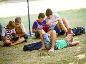 An image of young students relaxing on the grass at an English language school, linking to a page on Summer camps for children and young teenagers