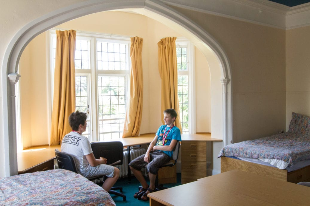 Two students talking at long desk in multi-bed room at Sir Henry residential English summer camp