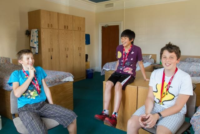 Three students in multi-bed room with desks and wardrobes at Sir Henry residential English summer camp