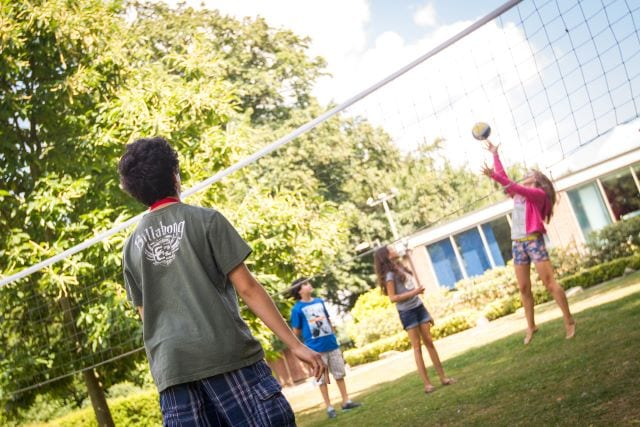 Students playing volleyball on lawns at Hockerill College for an activity at Sir Henry residential English summer camp