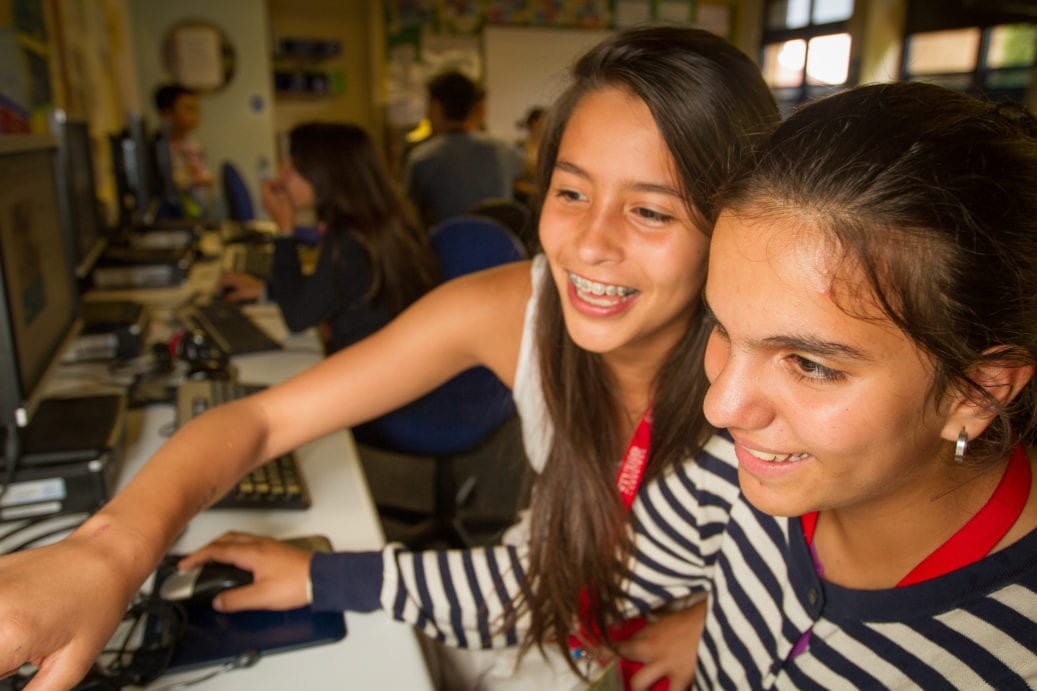 Two students laughing while using King's Ely computers at Sir Edward residential English summer camp