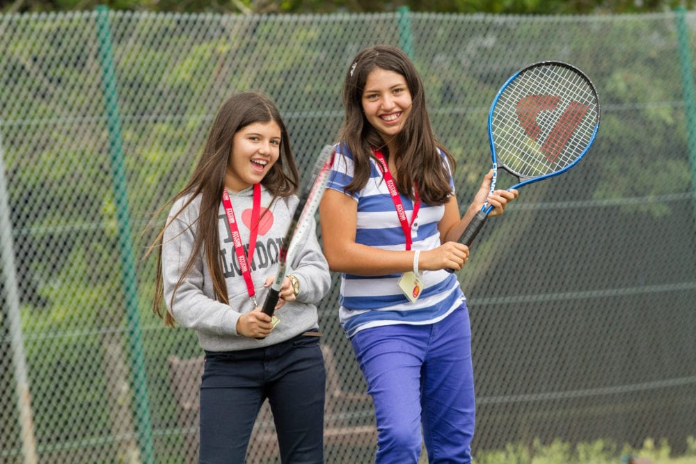 Two students at Sir Edward residential English summer camp pose with tennis rackets on courts in King's Ely