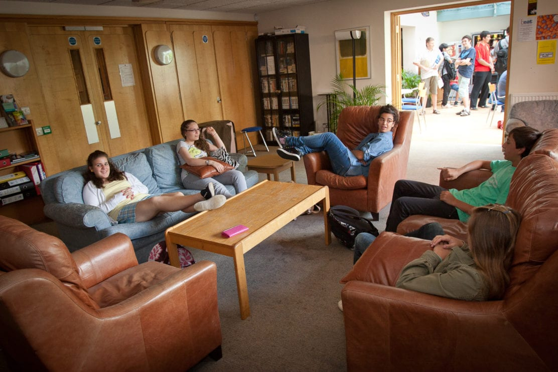 Students at Sir Laurence residential English summer camp make friends in a common room in Lucy Cavendish college