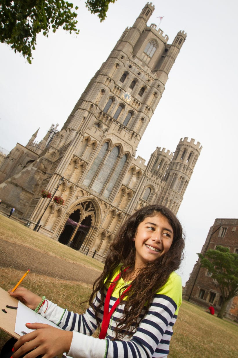 Student looks up from drawing Ely cathedral on art activity at Sir Edward residential English summer camp