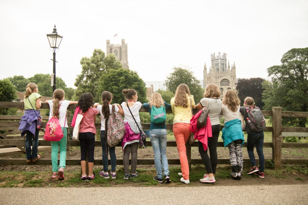 Line of students from Sir Edward residential English summer camp lean on fence and look at Ely cathedral