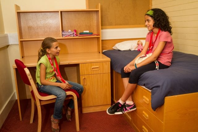 Two students chat in bedroom with desk and storage space at Sir Edward residential English camp