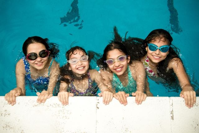Four students wearing goggles and smiling in pool at Sir Edward residential English summer camp