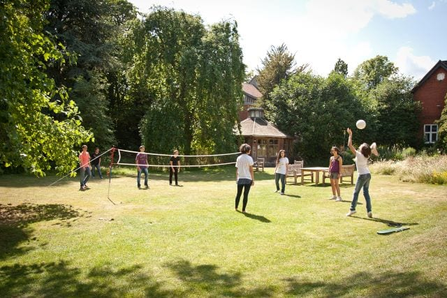 Students play volleyball on lawns of Lucy Cavendish college, base for Sir Laurence residential English summer camp
