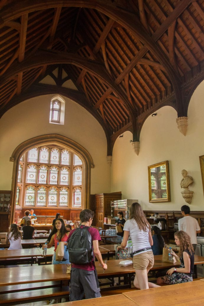 Students at Sir Christopher Cambridge summer camp sit with friends in magnificent Cambridge college dining hall