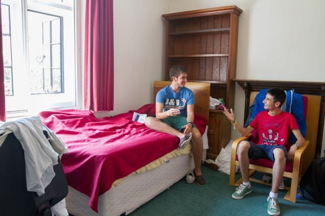 Two international students chat in single bedroom at Sir Christopher residential English summer camp