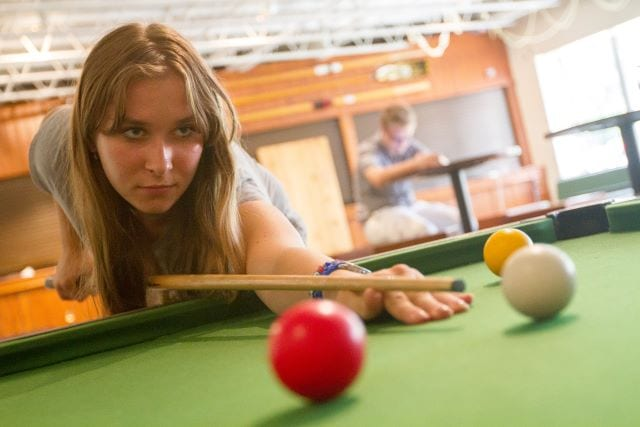 Student prepares to take a shot at snooker table in Sir Christopher residential English summer camp common room
