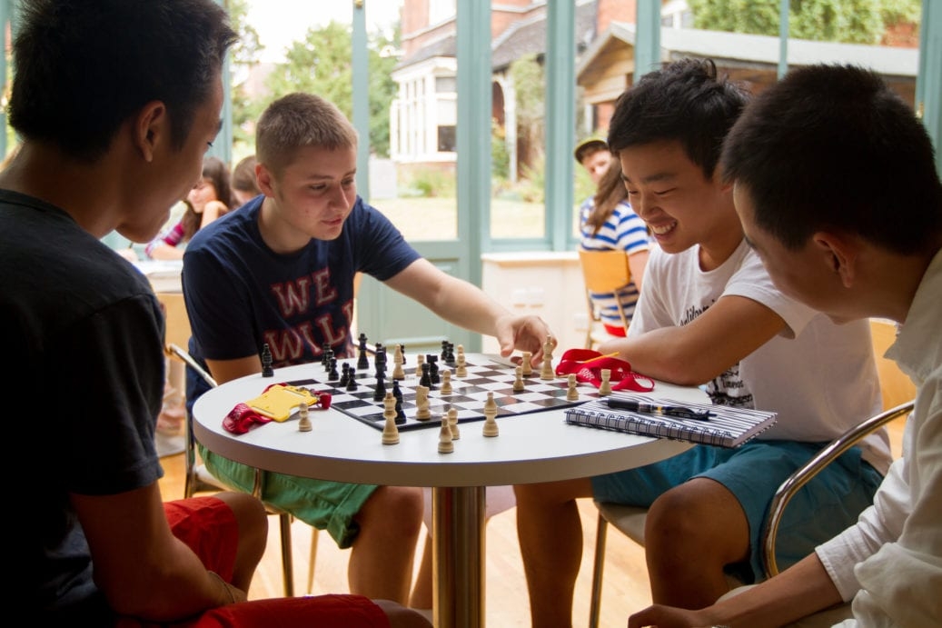 Group of students of Sir Laurence English residential summer camp gathered round a chess board as one student moves a piece