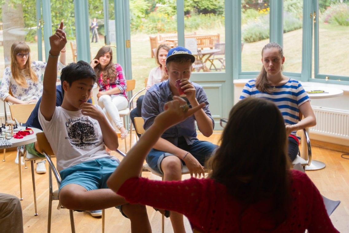 Teacher answers student question in English language lesson at Sir Laurence residential summer camp