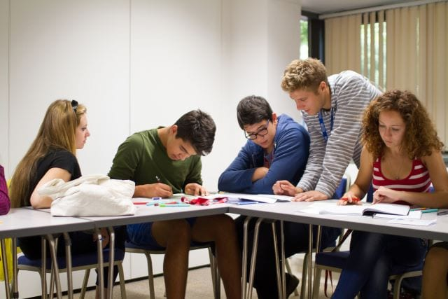 Teacher helps students in class at Sir Laurence residential English summer camp