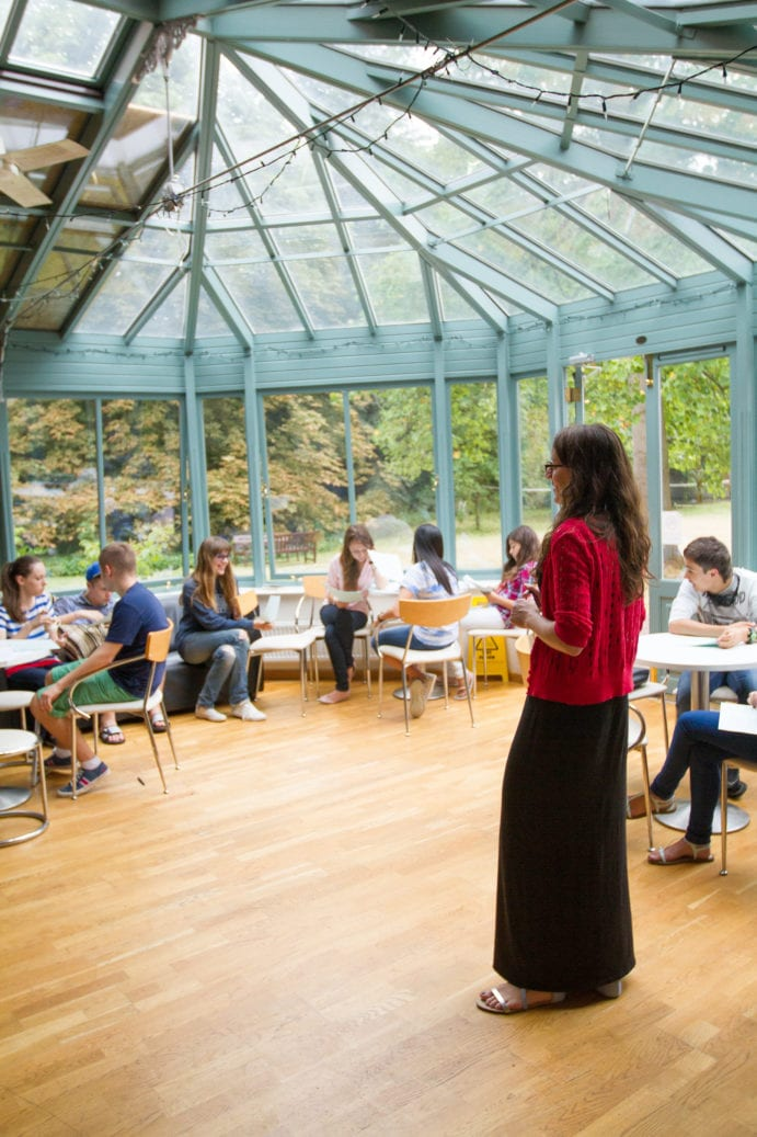 Studio Cambridge English teacher supervises group language work in airy conservatory at Sir Laurence residential English summer camp, Cambridge