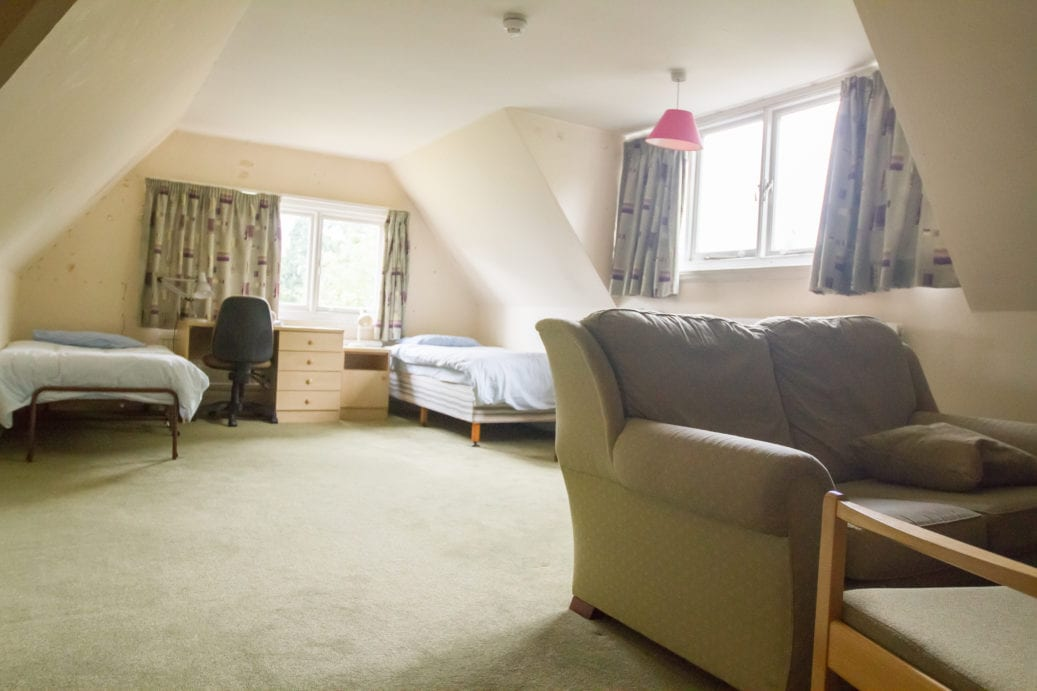 Spacious twin room with desk and comfortable chairs at Lucy Cavendish where Sir Laurence residential English summer camp is based