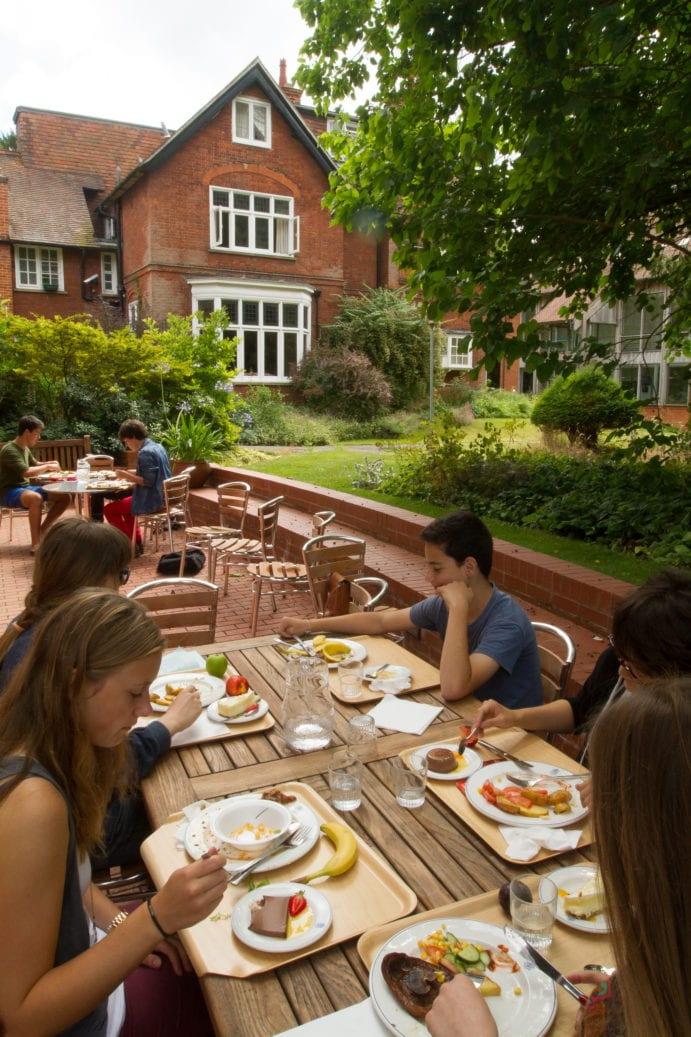 Students eating in enclosed lawns at Lucy Cavendish, base of Sir Laurence residential English summer camp