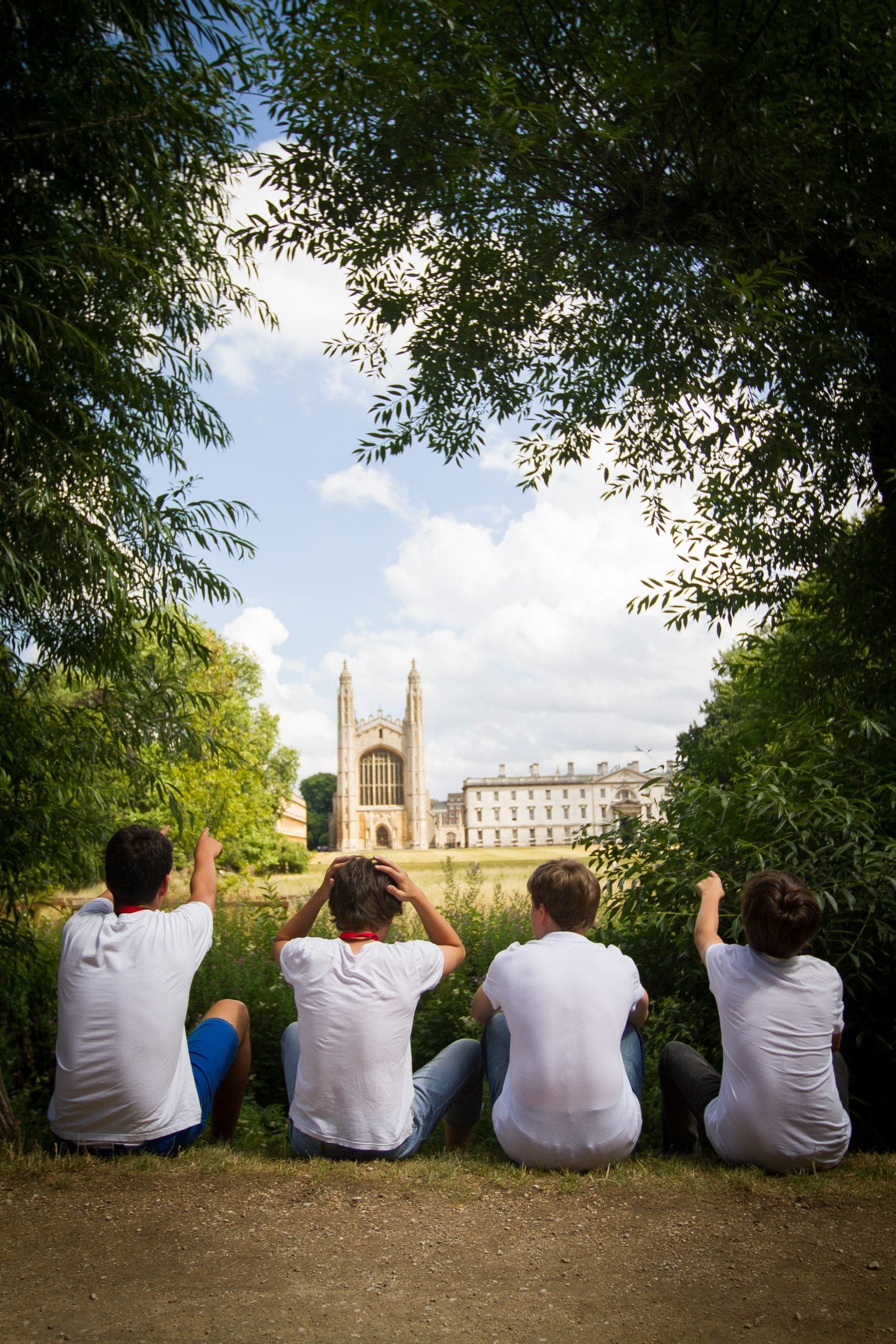 Four students on the Backs of the River Cam, looking at King's College Chapel, Cambridge