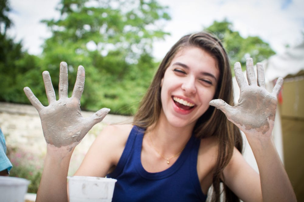 Student laughs as she holds up hand with clay on them for an activity at Sir Michael English summer camp, Cambridge