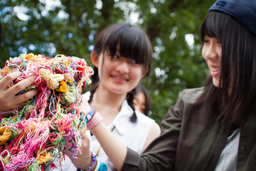 Two students hold up different coloured thread to use in craft activity at Sir Michael English summer camp in Cambridge