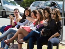 An image of a group of students sat on a bench together in the sun at an English language school, linking to a page on Summer camps for teenagers and young adults