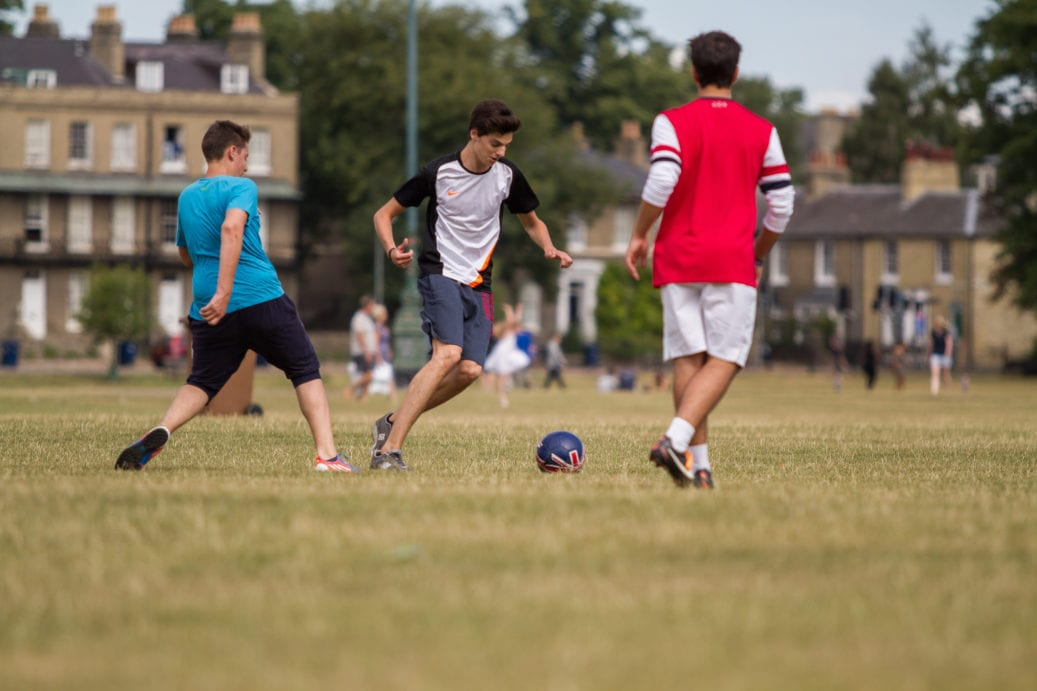 Students at Sir Michael English summer camp playing football on Parker's Piece in Cambridge