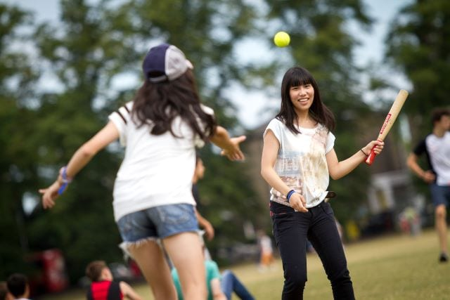 Student pitches to student with rounders bat during sports activity at Sir Michael English summer camp