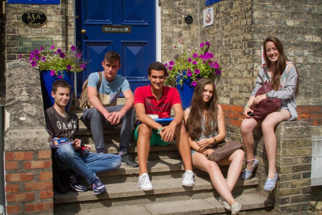 Students sit on steps outside Studio Cambridge Main School in Cambridge, UK.