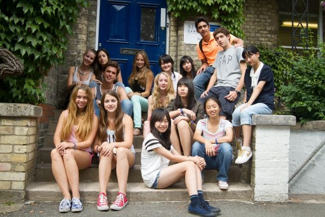 Large group of students chat and laugh on steps outside Studio Cambridge Main School, where English lessons for Sir Michael English summer camp are held