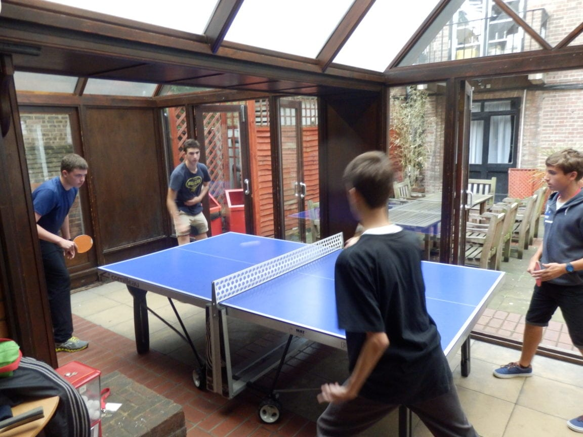 Four students at Sir William residential English summer camp in London play table tennis in their free time