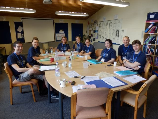 The welfare team at Sir Edward residential English summer camp sit around a table at a meeting, smiling