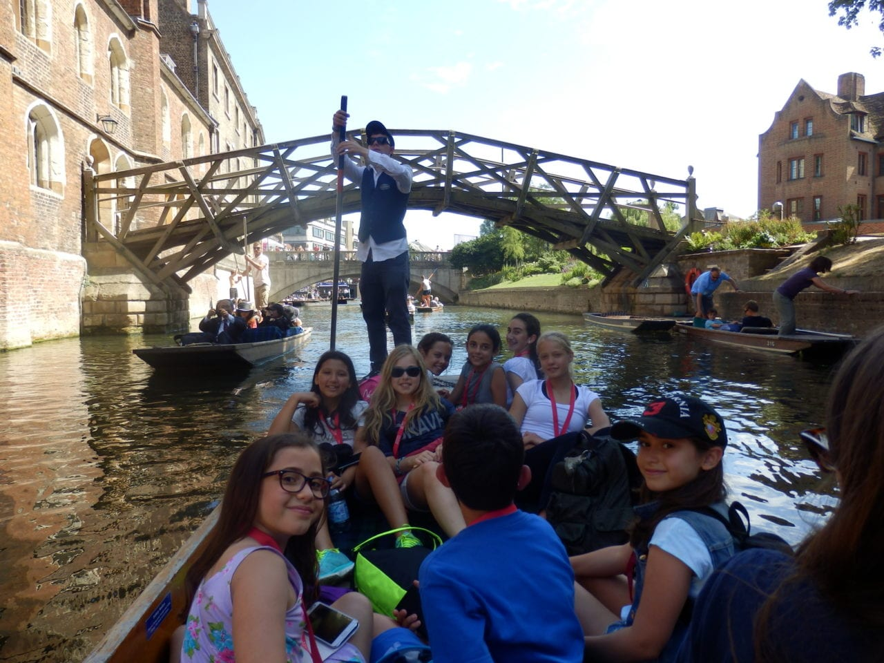 Students at Sir Edward residential English summer camp in punt on River Cam with Mathematical bridge in background