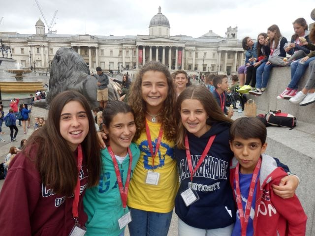 Five students smile at the camera in front of Trafalgar Square on excursion at Sir Edward residential English summer camp