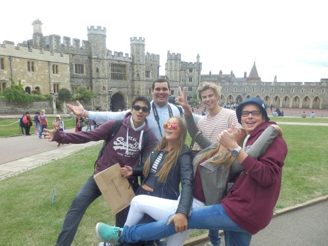 Students pose in courtyard of old English castle on excursion at residential English summer camp, Studio Cambridge.