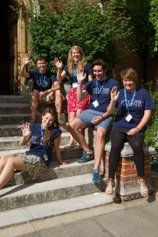 Residential Activity Organisers at Sir Christopher residential English summer camp wave on steps of Ridley Hall College