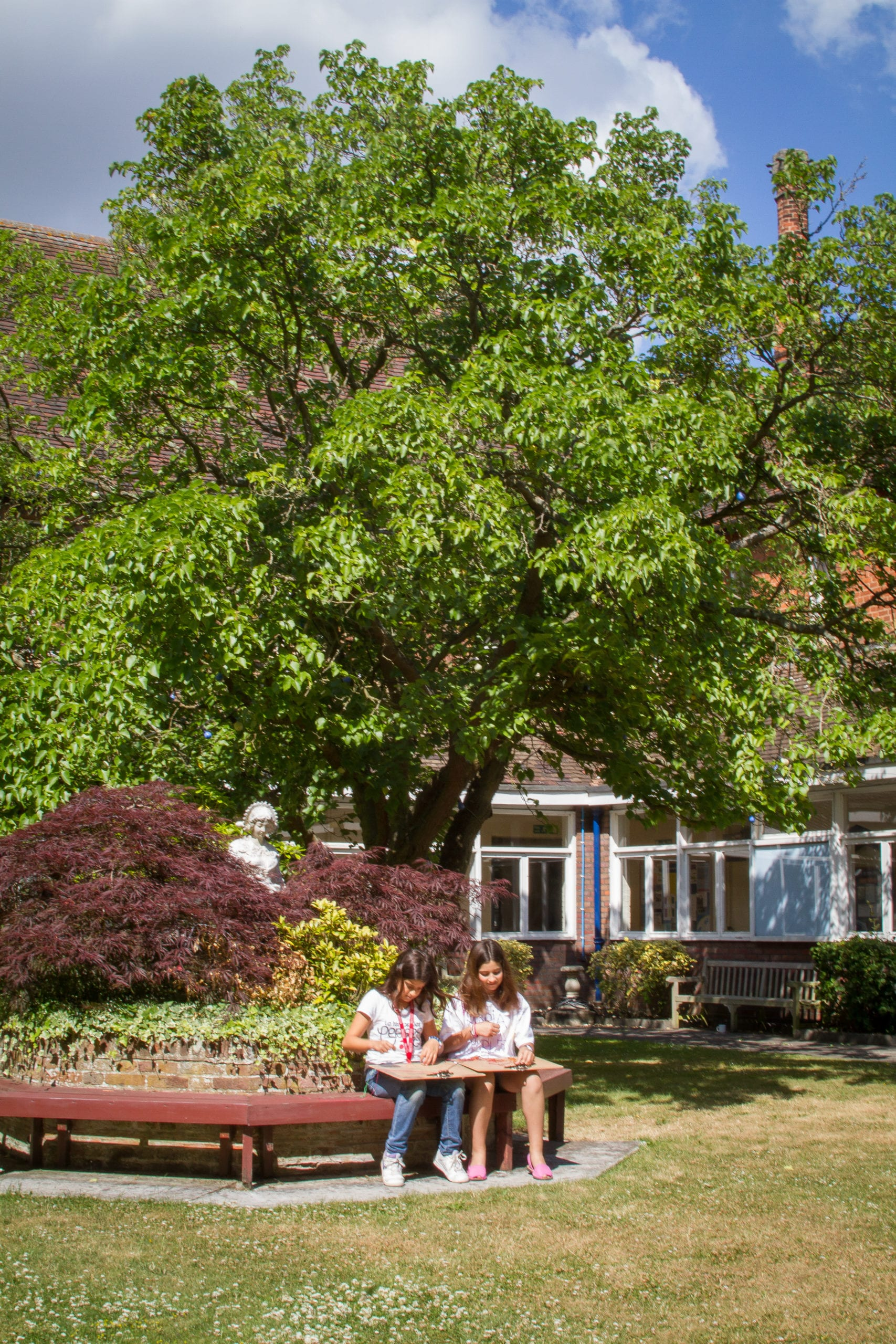 Two students sit on bench circling flowerbeds on Hockerill College lawns, where Sir Henry residential English summer camp is based